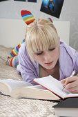 Постер, плакат: Полная длина молодая студентка писать в книге лежа на кровати