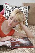 Постер, плакат: Красивая девочка подросток читая журнал лежа в постели