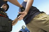foto of policeman  - Low angle view of policeman arresting criminal against sky - JPG