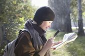 picture of glass-wool  - Side view of a smiling woman looking at map with magnifying glass outdoors - JPG
