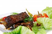 meat plate: grilled ribs on white plate with red hot peppers, tomatoes and chives isolated over white background