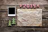 Sweet 2014 New Year holiday background. With blank instant photo frame, crumpled paper sheet and cute Christmas trees.