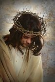 Portrait of Jesus with crown of thorns over old wall background