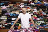 Portrait of confident fabric store owner standing at counter