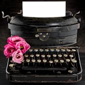 stock photo of old vintage typewriter  - Old antique black vintage typewriter and empty paper for copy space with red romantic flowers - JPG