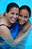 Mother And Daughter Hugging In A Pool.