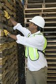 pic of wooden pallet  - Side view of a man inspecting wooden pallets in distribution warehouse - JPG