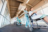 Low angle view of female nurses pushing patients on wheelchairs with doctor walking at corridor in h