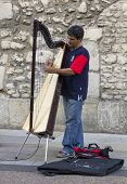 A Street Musician Plays The Harp In Broad Street, Oxford, England