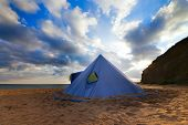 foto of conic  - Conical tent on summer beach and blue sky with clouds - JPG