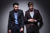 two hot male models posing against studio background, one looking away and one unbuttoning his suit