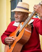 HAVANA,CUBA - JANUARY 15, 2014:Old afrocuban street musician playing the guitar next to a colonial house.2 850000 foreign tourists visited Cuba in 2013,many of them attracted by its distinct culture