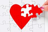 A woman putting the missing piece of a jigsaw red heart in place, good image to represent a love, br