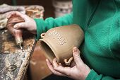 Potter Decorating A Ceramic Jar With The Word Honey