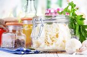 Composition with fresh and marinated cabbage (sauerkraut), spices, on wooden table, on bright background