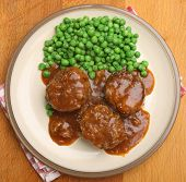 Faggots (traditional offal meatballs) with peas and gravy.
