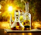 Olive Oil on the Table in garden of Olive Trees. Sun. Healthy eating concept. Mediterranean cuisine.