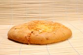 stock photo of flat-bread  - Round flat loaf of white bread with cheese - JPG