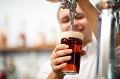 stock photo of drawing beer  - Detail of a bartender brewing a beer - JPG