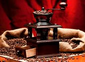 Manual coffee grinder with coffee beans on red background