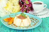 Panna Cotta with orange zest and caramel sauce, on color wooden background