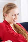Beautiful caucasian woman sitting ona couch and wearing red pullover. Indoor background.