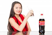 NAKHODKA, RUSSIA - JANUARY 18, 2014: Girl holding a glass of Coca-Cola on the table is a bottle of Coca-Cola. Coca-Cola is a very popular carbonated soft drink sold in stores, restaurants worldwide.