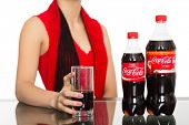 NAKHODKA, RUSSIA - JANUARY 18, 2014: Girl holding a glass of Coca-Cola on the table is a bottles of