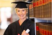 stock photo of laws-of-attraction  - elegant middle aged female law school graduate in library - JPG