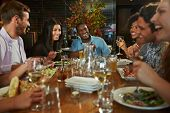 stock photo of chinese restaurant  - Group Of Friends Enjoying Meal In Restaurant - JPG