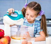 image of human egg  - little girl with a mixer whisk the eggs in the kitchen at home - JPG