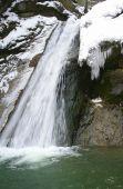 Small mountain creek with waterfall in winter