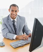 Portrait of a smiling young businessman using computer at office desk