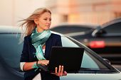 Young business woman with laptop on the car parking