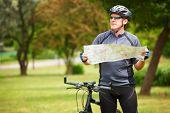 Man on bike checking map.
