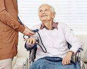 Nurse measuring blood pressure for senior woman in wheelchair in a nursing home