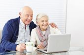 Happy senior citizen couple using laptop computer at home
