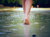 stock photo of footprint  - Girl walking on sand beach leaving footprints - JPG