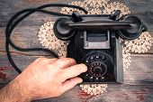 stock photo of rotary dial telephone  - Man making a call on a rotary telephone dialing the numbers with his finger high angle view of the instrument on an old wooden surface - JPG
