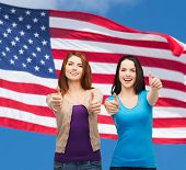 friendship and happy people concept - two smiling girls showing thumbs up over american flag background