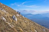 Two hikers on trekking through mountain Rtanj on a sunny day