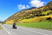 Great Highway in Austrian Alps. Among the picturesque hills at high speed riding two motorcycles biker