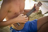boy playing the ukulele