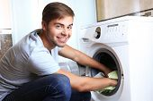 Housework: Man loading clothes into washing machine
