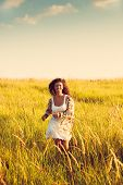smiling woman wearing boho style clothes run through the grass, hot summer day, retro colors