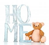 Decorative letters forming word HOME with teddy bear isolated on white