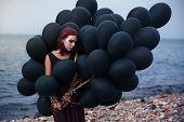Beautiful girl walking with black balloons