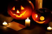 Halloween pumpkins with candles and post card isolated on black background
