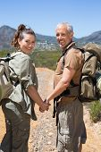 Happy hiking couple standing on mountain trail holding hands on a sunny day