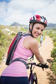 Fit couple cycling on mountain trail woman smiling at camera on a sunny day